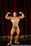 Assuming a classic bodybuilding pose this professional competitor displays his perfectly fit massively muscled body on stage. The man has his arms up flexing his biceps and is facing the audience and camera.